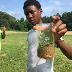 Youth holding soil sample in the field.